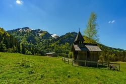 little wooden chapel with single tree on the high moor in Bregenz forest, with trees, forests and mountains in background. spring, Vorarlberg, Austria. shingled chapel with little tower at a sunny day