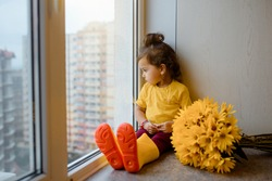 Little 2 year child girl in a yellow t-shirt and yellow rain boots is sitting on a window sill near a vase with yellow flowers and looking through the window.