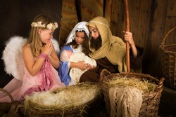 Little 7 year old angel visiting a nativity scene reenacted with a doll