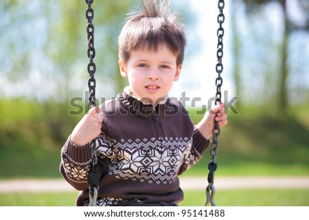 Little 3 year old boy on swing in playground outdoors