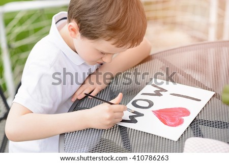 Little 7 year old boy paints greeting card for Mom on Mother\'s Day with the inscription \