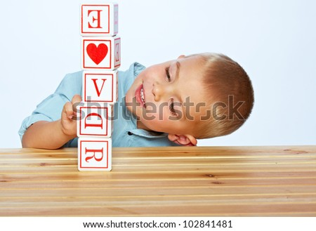 little 3 year old toddler boy playing with wooden abc alphabet blocks on the light blue studio background
