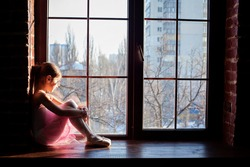 little young ballerina posing on camera. Little girl training to be a ballerina standing in a graceful arms raised position in pink satin ballet shoes in a bright sunlit ballet studio near the window