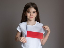 Little / young girl with long hair in a white T-shirt holds the Polish flag. Language school concept. Learning Polish. Immigration to Poland