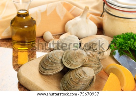 Littleneck clams arranged with ingredients for preparing baked clams - shellfish are a delicious meal but also a represent a dangerous food allergen