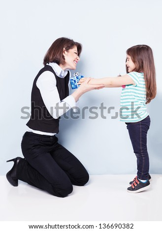 littler cute girl giving her mom a present on blue background