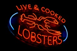 Live and cooked lobsters old and dusty vintage fluorescent neon store sign at a fish market