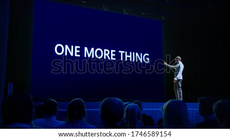 Photo of  Live Event with Brand New Products Reveal: Keynote Speaker Presents New Device to Audience. Movie Theater Screen Shows Text -one more thing-