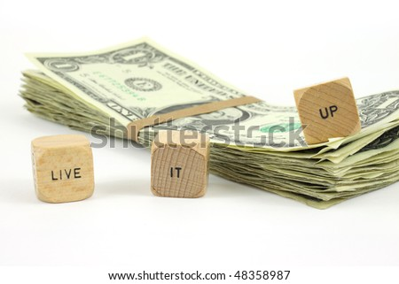Live it up wood dice with cash on a white background