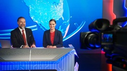 Live News Studio with Beautiful Female and Handsome Man Anchors Start Reporting. TV Broadcasting Channel with Presenters Talking. Television Newsroom Set. Behind the Scene Camera Shooting Shot