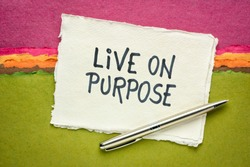 Live on purpose inspiraitonal note - handwriting on a handmade rag paper against abstract landscape, personal devleopment, goals and lifestyle concept