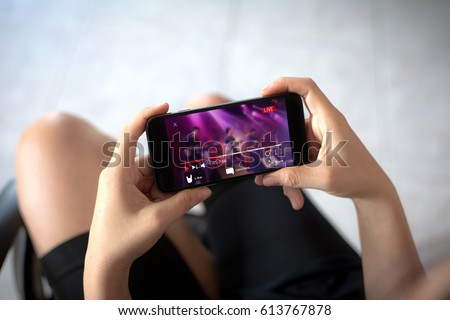 Live video streaming concept.Female hands holding mobile phone #613767878