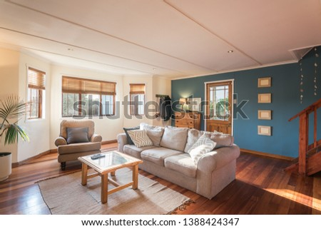 Lived in contemporary living room with wooden floor, decorated with couch, coffee table, drawers, lamp, pictures on the wall, view to garden #1388424347