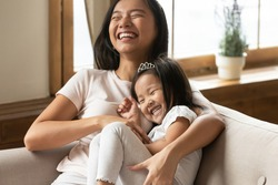 Lively asian young mother tickling little daughter enjoy free time active weekend together, wearing casual comfortable home clothes kid girl tiara accessory, beautiful happy family having fun concept