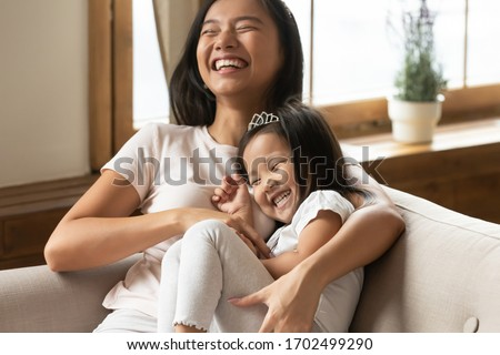 Lively asian young mother tickling little daughter enjoy free time active weekend together, wearing casual comfortable home clothes kid girl tiara accessory, beautiful happy family having fun concept stock photo