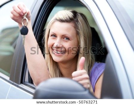 Lively female driver showing a key with a thumb up after buying a new car