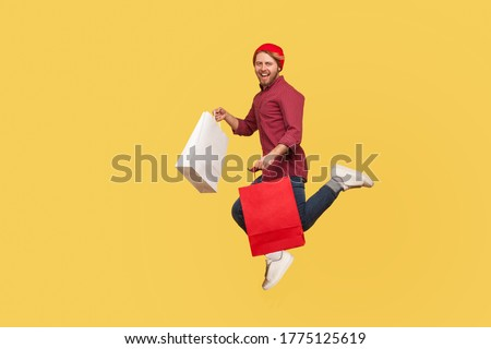Lively happy hipster trendy guy running in air with shopping bags in hands, hurrying to catch sale, flying and rushing for thrift discount. full length studio shot isolated on yellow background Stockfoto ©