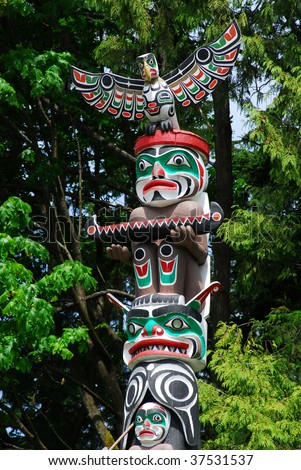 Lively historic totem pole by ancient native indian americans in the stanley park, Vancouver, British Columbia, Canada - stock photo