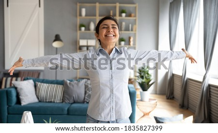 Lively Indian girl having wide smile standing with arms stretched eyes closed enjoy weekend at new house feels free from life troubles, sunlight illuminates cozy room. Welcoming new happy day concept