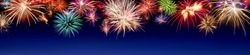 Lively multi-colored fireworks on dark blue background in panorama format, ideal for New Year or other celebration events