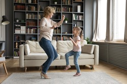 Lively vivacious middle-aged grandmother dancing with little five years old granddaughter in cozy living room at home. Active multi-generational family fooling around and having fun together concept