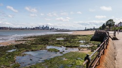 Liverpool skyline over the rockpools seen at low tide from the promenade at New Brighton in August 2020.