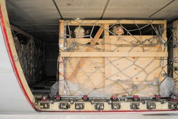 Livestock in wooden boxes secured by nettings being shipped in the lower cargo hold of a Jumbo Jet freighter aircraft