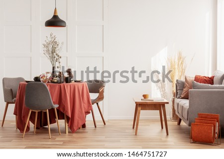 Living and dining room interior with grey couch and table covered with orange tablecloth