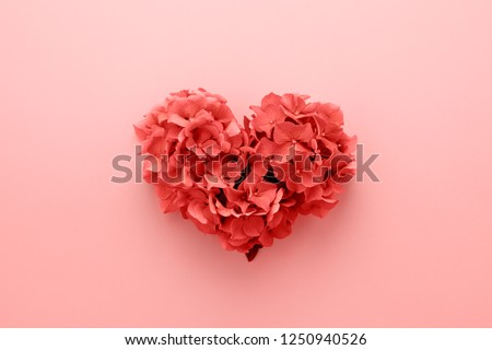 Photo of Living Coral color of the Year 2019. Heart shape made of flowers. Valentine's day. Color palette. Love fashion