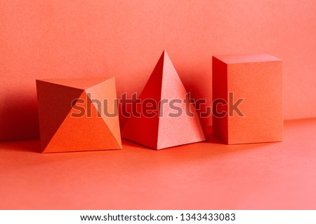 Living coral trend color geometrical figures still life composition. Beautiful three-dimensional pyramid rectangular cube objects. Platonic solids figures, simplicity concept photography.
