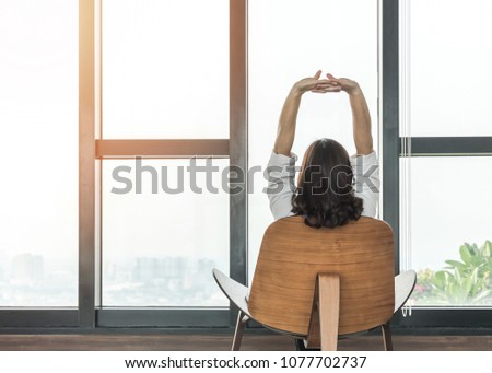 Living lifestyle, luxury simplicity home relaxation life style of happy working woman take it easy sitting resting on comfort chair at home, condominium or city hotel lobby interior with rooftop view