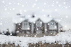 Living place in winter, snowfall. December. Defocused country house with car and fence in snow. Wooden plank in snow in front side.
