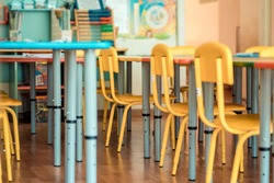 Living room: Chairs, table and toys. Interior of kindergarten. Soft selective focus.