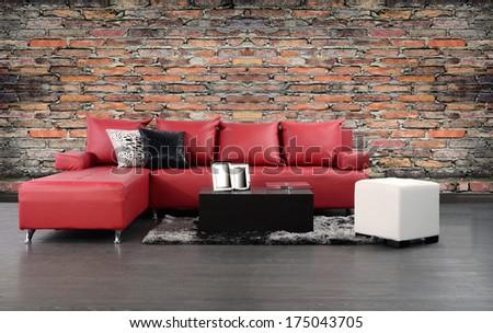 Living room. Furniture on hardwood floor against rough brick wall.