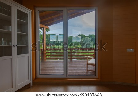 Living room in a wooden organic house. Wooden floor, wooden ceiling. Corky walls. White cupboard. Panoramic windows looking over wooden terrace around the house.  #690187663
