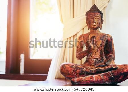 Living room interior decor: buddha statue on the table near the window