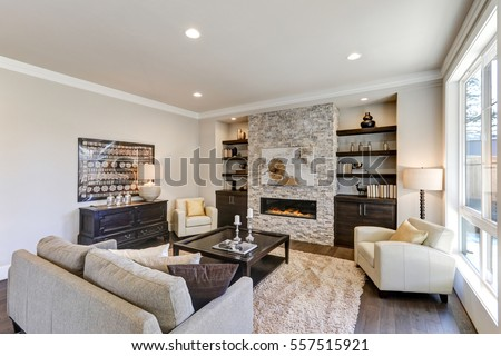 Living room interior in gray and brown colors features gray sofa atop dark hardwood floors facing stone fireplace with built-in shelves. Northwest, USA  #557515921