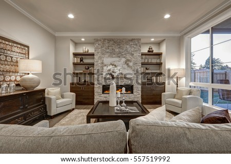 Living room interior in gray and brown colors features stone fireplace with built-in shelves and cabinets, large dark stained cocktail table atop beige fluffy rug and large window.  Northwest, USA  #557519992