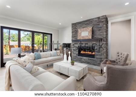 Living room interior in new luxury home with fireplace and hardwood floors.