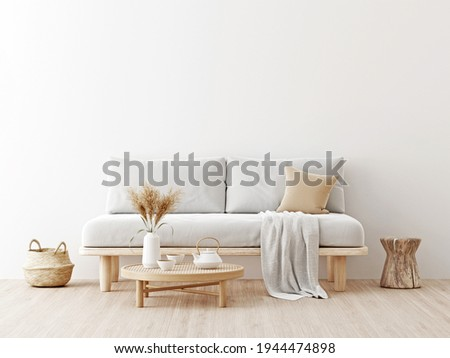Living room interior wall mockup in warm neutrals with low sofa, dried Pampas grass, caned table, trendy basket and japandi style decor on empty white wall background. 3D rendering, illustration.