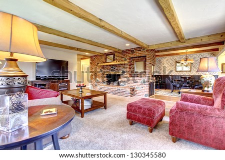 Living room interior with brick fireplace, wood beams and red.