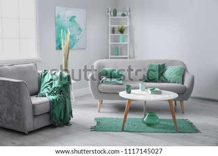 Living room interior with comfortable armchair and sofa. Mint color decors