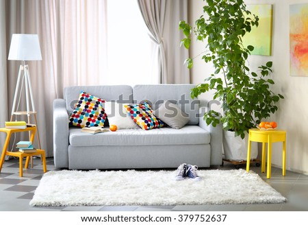 Shutterstock Living room interior with sofa, lamp and green tree