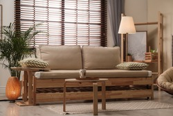 Living room interior with sofa, window blinds and stylish decor elements