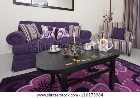 Living room lounge in a luxury apartment showing purple interior design