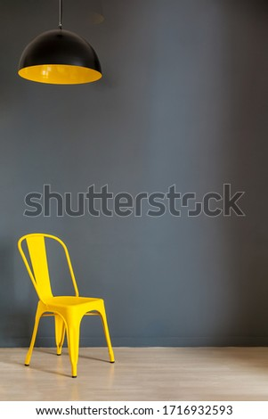Living room wall mock up with dark grey wall and bold yellow chair and lamp. Illuminating Yellow and Ultimate Gray, colors of the year 2021