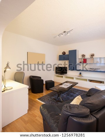 Living room with black leather sofa and parquet. Nobody inside