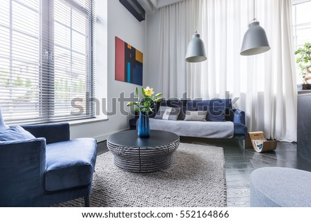Living room with blue upholstered furniture, window blinds and white net curtain #552164866