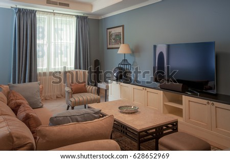 Living room with blue walls, TV, sofa, bookcase, carpet, lamps and coffee table #628652969