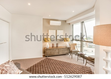 Living room with city view near glass windows, tiled floor near walls, sofa set with pillows, lamps on the wooden table, walls are white color, floor carpet has some designs.